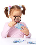 Girl is looking at euro banknote using magnifier Stock Images