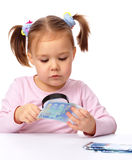Girl is looking at euro banknote using magnifier Royalty Free Stock Photography