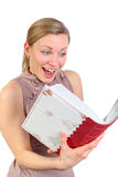 Girl looking excited into a photo album. Blonde female looking very excited into a book or photo album (isolated on white Stock Image
