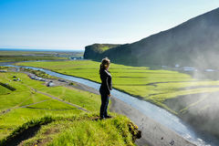 Girl looking at famous Skogafoss Waterfall, Iceland Stock Images