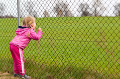 Girl looking through fence. Rear view of girl in pink clothes looking through metal fence with green field in background Royalty Free Stock Images