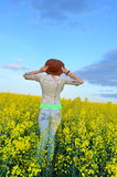 Girl looking at field of yellow flowers Stock Image