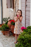 Girl looking at flowers. Pretty little girl surrounded by plant pots looking at flowers she is holding in her hands Royalty Free Stock Photography