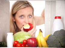 Girl looking at food in fridge stock photo