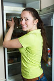 Girl looking in fridge. Happy girl looking for something in fridge at kitchen Stock Images