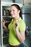Girl looking in fridge. Happy young girl looking for something in fridge at kitchen Stock Photography