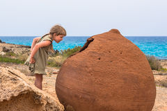 Girl looking into a giant pot on Nissi Beach, Ayia Napa, C. A girl looking into a giant old pot on Nissi Beach, Ayia Napa, Cyprus Stock Image