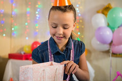 Girl looking at gift bag during birthday party Royalty Free Stock Image