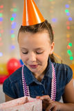 Girl looking at gift bag during birthday party Stock Image