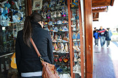 Girl looking at a gift shop. Mar del Plata, Argentina - September 24, 2012: A girl looking outside of a gift shop in the  port of the coastal city of  Mar del Stock Image