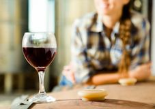 Girl looking at glass of red wine standing on wooden barrel in w. Girl looking at glass of wine standing on wooden barrel in winery royalty free stock images