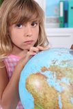 Girl looking at a globe Stock Images