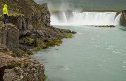 Girl looking at Godafoss waterfall Stock Photo