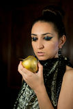 Girl looking at a golden apple Stock Images