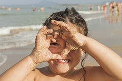 Girl looking through a heart draw with her hands. Beach. Royalty Free Stock Photos