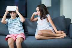 Girl looking at her brother using virtual reality headset in living room Stock Photos