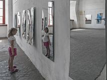 A girl looking at her image in the distorted mirror in the hall of mirrors. The unidentified girl looking at her image in the distorted mirror in the hall of Royalty Free Stock Images