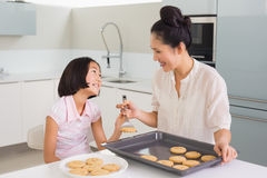 Girl looking at her mother prepare cookies in kitchen Royalty Free Stock Images