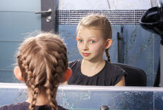 Girl looking at her reflection Royalty Free Stock Photos