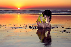 Girl looking at her reflection. Little girl looking at herself in the water during sunset Royalty Free Stock Image