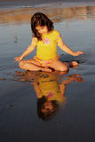 Girl looking at her reflection. Little girl looking at herself in the water during sunset Stock Photo