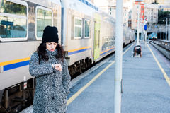 Girl looking at her watch and standing next to a train close up. Girl with grey coat and black hat looking at her watch and standing next to a train Royalty Free Stock Photos