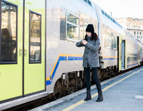 Girl looking at her watch and standing next to a train Stock Photos