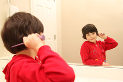 Cute girl combing hair while looking in the mirror Royalty Free Stock Image