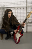 Girl looking his electric guitar. Beauty woman in black jacket and guitar in prison looking his electric guitar Royalty Free Stock Photo