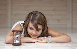 Girl  looking at an hourglas. Girl lying on the floor and looking at an hourglass Royalty Free Stock Images