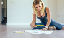 Girl looking house plans. Sitting on the floor royalty free stock photography