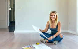 Girl looking house plans. Sitting on the floor stock photography