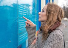 Girl looking for job on board. Side view of woman in coat outside exploring information board on street reading news and searching job stock photos