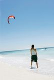 Girl looking at kite surfer. In the sea Stock Image