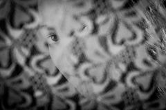 Girl looking through a lace curtain Royalty Free Stock Image
