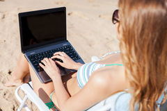 Girl looking at laptop on the beach Royalty Free Stock Photography