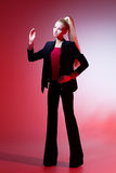 Girl looking like Barbie doll. Beautiful blond girl in black suit and red top looking like Barbie doll royalty free stock images