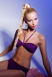 Girl looking like Barbie doll. Beautiful blond girl in purple bikini looking like Barbie doll stock photos