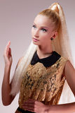 Girl looking like Barbie doll. Portrait of beautiful blond girl in golden dress looking like Barbie doll royalty free stock photo