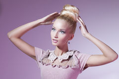 Girl looking like Barbie doll. Portrait of beautiful blond girl in pink dress looking like Barbie doll over pink background royalty free stock photography
