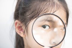 Girl looking through magnifier. Royalty Free Stock Images