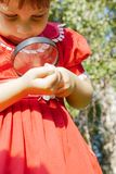 Girl looking through magnifiying glass at grass Royalty Free Stock Photography