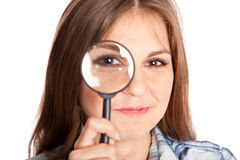 Girl is looking through magnifying glass Stock Image