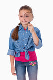 A girl looking through a magnifying glass Stock Photo