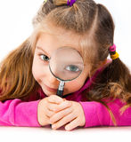Girl looking through a magnifying glass Stock Photos