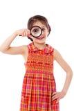 Girl looking through a magnifying glass Stock Photos