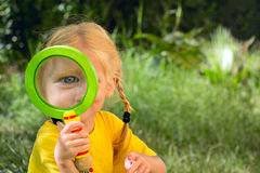 Girl looking through a magnifying glass Royalty Free Stock Photo