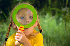 Girl looking through a magnifying glass Stock Photo