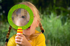 Girl looking through a magnifying glass Royalty Free Stock Images