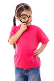 Girl looking through a magnifying glass Royalty Free Stock Photography
